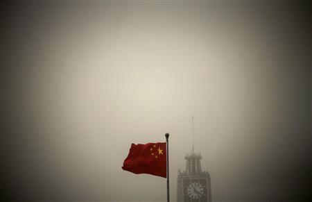 A Chinese national flag flies in front of Beijing Telegraph Building on a hazy morning in central Beijing in this February 28, 2013 file photo. REUTERS/Petar Kujundzic/Files