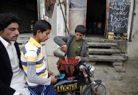 A boy fills the tank of a motorbike with smuggled petrol along a roadside shop in Quetta February 13, 2013. The black sign board reads ''Agha Jan today's rate, petrol 105 Pakistani rupee ($1) litre and diesel 95 Pakistani rupee ($ 0.96) litre. REUTERS/Naseer Ahmed/Files