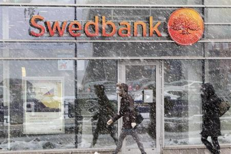 People walk past a Swedbank branch in Riga February 14, 2012. REUTERS/Ints Kalnins
