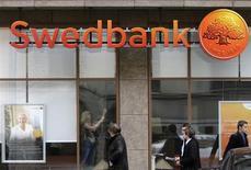 Люди проходят мимо отделения Swedbank в Риге 4 июня 2009 года. Шведский Swedbank сворачивает свой бизнес в России и на Украине, сосредоточившись на домашних рынках и в Прибалтике, сообщил банк в понедельник. REUTERS/Ints Kalnins