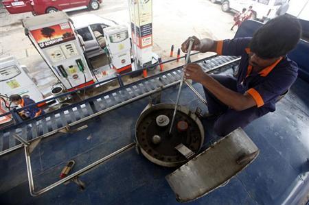 An employee measures diesel in a tanker before unloading at a fuel station in Kolkata August 13, 2012. REUTERS/Rupak De Chowdhuri/Files