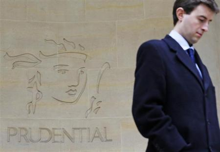 A man walks past a Prudential sign outside offices in the City of London March 27, 2013. REUTERS/Luke MacGregor