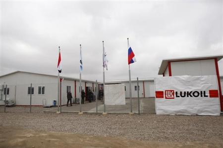 People stand at the headquarters of Russian oil firm LUKOIL in the West Qurna-2 oilfield located in the southern city of Basra December 25, 2012. REUTERS/Atef Hassan