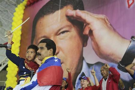 Venezuela's acting President Nicolas Maduro carries a child dressed as national hero Simon Bolivar in front of a poster of late president Hugo Chavez during a campaign rally in the state of Lara March 24, 2013 in this picture provided by the Miraflores Palace. REUTERS/Miraflores Palace/Handout