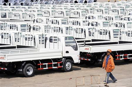 A worker walks past Chinese trucks for exporting at a port of Liangyungang, Jiangsu province, March 31, 2013. China's official manufacturing purchasing managers' index (PMI) released by the National Bureau of Statistics rose to an 11-month high of 50.9 in March, above the 50-point level that indicates growth on the month. Picture taken March 31, 2013. REUTERS/China Daily