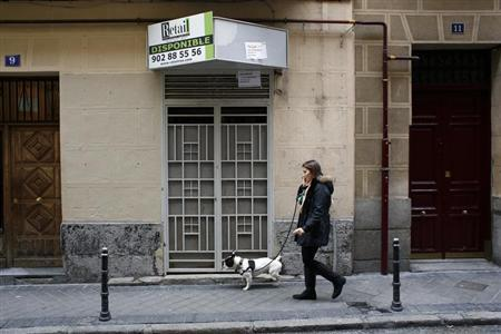 A woman walks past a closed down business in Madrid March 27, 2013. REUTERS/Juan Medina