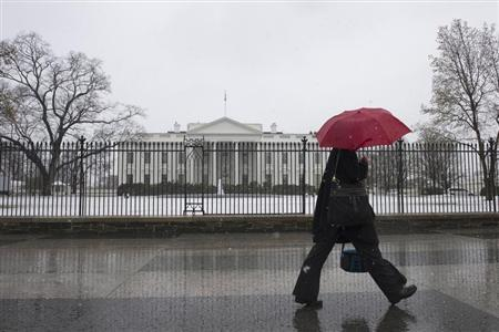 A pedestrian walks down Pennsylvania Avenue past the White House during an early spring snowstorm, in Washington March 25, 2013. REUTERS/Mary F. Calvert
