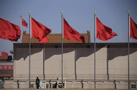 A paramilitary policeman stands guard under flags outside the Great Hall of the People during the third plenary session of the National People's Congress (NPC) in Beijing March 10, 2013. REUTERS/Petar Kujundzic