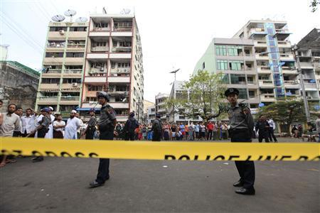 Police stand near a mosque and school dormitory that were damaged by a fire in Yangon April 2, 2013. REUTERS-Soe Zeya Tun