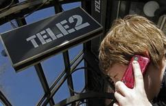 Мужчина говорит по телефону у отделения оператора Tele2 в Санкт-Петербурге 28 марта 2013 года. Сделка Tele2 и российского ВТБ по продаже российских активов скандинавского оператора госбанку - дело решенное и пересматриваться не будет, сообщила Tele2 во вторник. REUTERS/Alexander Demianchuk