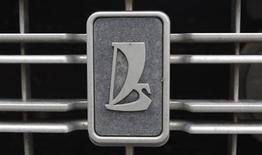 Логотип Автоваза на решетке радиатора автомобиля в Санкт-Петербурге 2 мая 2012 года. Флагман отечественного автопрома Автоваз снизил продажи автомобилей Lada в России в марте на 7,1 процента в годовом выражении до 40.480 штук, сообщила компания, сославшись на спад авторынка, снижение спроса на машины эконом-класса, а также ожидание начала продаж новой версии модели Lada Kalina. REUTERS/Alexander Demianchuk