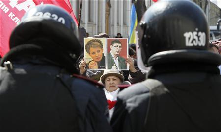 A Ukrainian opposition supporter holds a placard displaying former Ukrainian Prime Minister Yulia Tymoshenko (L) and former Interior Minister Yuri Lutsenko during a rally in Kiev, April 2, 2013. REUTERS/Gleb Garanich