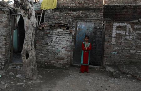 A girl stands beside her house at a slum in Islamabad March 25,2013. REUTERS/Zohra Bensemra