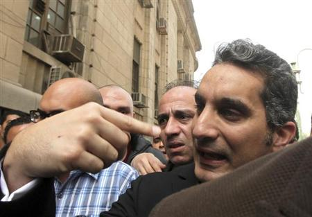 Bassem Youssef (R), the country's best-known satirist, gestures to journalists and activists as he arrives at the high court to appear at the prosecutor's office in Cairo March 31, 2013. REUTERS/Mohamed Abd El Ghany