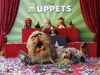 Muppet character Sweetums holds a commemorative plaque as he lies beside the newly unveiled Muppets star as other Mupetts background (L-R) Animal,Pepe, Miss Piggy, Fozzie and Gonzo and bottom row Kermit and Walter take part in ceremonies honoring the Muppets with a star on the Hollywood Walk of Fame in Hollywood, California March 20, 2012. REUTERS/Fred Prouser
