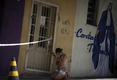 A woman kneels next to the Boate Kiss nightclub, in the southern city of Santa Maria, 187 miles (301 km) west of the state capital Porto Alegre, January 29, 2013. REUTERS/ Ricardo Moraes