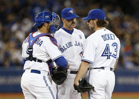 Toronto Blue Jays pitching coach Pete Walker (C) talks with starting pitcher R.A. Dickey and catcher J.P. Arencibia during the sixth inning against the Cleveland Indians in their MLB American League baseball game in Toronto, April 2, 2013. REUTERS/Mark Blinch