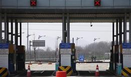 Южнокорейские солдаты идут по пустой дороге, соединяющей промышленную зону Кэсон и южнокорейский пункт таможенного и паспортного контроля, в Пхаджу 3 апреля 2013 года. Северная Корея закрыла Южной доступ в совместную промышленную зону, от которой получает до $2 миллиардов в год, но позволит сотням граждан Южной Кореи вернуться домой, сообщили официальные источники, развеяв страхи Сеула о том, что их могли взять в заложники. REUTERS/Kim Hong-Ji