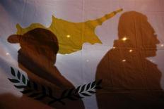 Тени участников акции протеста, проходившей возле президентского дворца в Никосии 27 марта 2013 года, на флаге Кипра. Кипр должен достичь первичного профицита бюджета в 4 процента ВВП начиная с 2017 года, чтобы гарантировать сокращение государственного долга, гласит меморандум о взаимопонимании между Никосией и международными кредиторами, где обговаривается помощь острову на сумму 10 миллиардов евро. REUTERS/Yorgos Karahalis