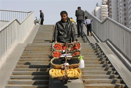 A street vendor pushes his mobile fruit stall on a pedestrian overpass in Beijing March 22, 2013. REUTERS/Kim Kyung-Hoon