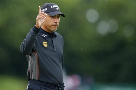 Jeev Milkha Singh acknowledges the crowd after making his birdie putt on the first green during the first round of the British Open golf championship at Royal Lytham & St Annes, northern England July 19, 2012. REUTERS/Brian Snyder/Files