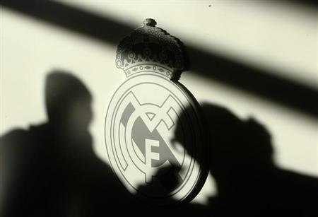 Shadows of reporters are seen on Real Madrid's logo during a news conference of Real Madrid new coach Juande Ramos ahead of their Champions League match against Zenit Saint Petersburg in Madrid December 9, 2008. REUTERS/Andrea Comas