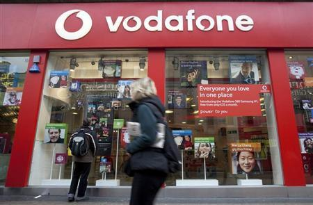 A pedestrian passes a Vodafone store on Oxford Street in central London, November 10, 2009. Vodafone, the world's largest mobile phone operator by revenue, has doubled its cost cutting target to 2 billion pounds by 2012, after a successful start to the programme boosted cashflow. REUTERS/Kevin Coombs