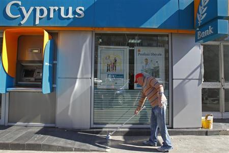 A worker sweeps in front of a branch of Bank of Cyprus in Bucharest April 1, 2013. REUTERS/Bogdan Cristel