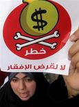 مصرية ترفع لافتة وتهتف أثناء مشاركتها في احتجاج أمام مكتب النائب العام بالقاهرة يوم الأربعاء احتجاجا على زيارة وفد صندوق النقد الدولي للعاصمة المصرية. تصوير: محمد عبد الغني - رويترز