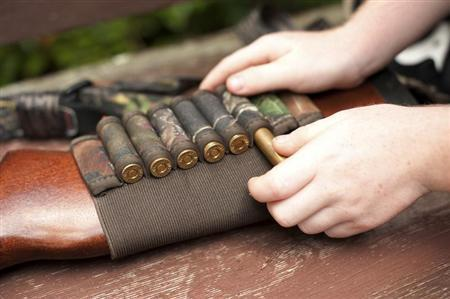 A 6-year-old boy prepares a gun before a hunt near Union Springs, Alabama June 16, 2012. REUTERS/Michael Spooneybarger
