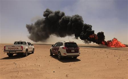 Police vehicles are seen next to a gas pipeline after an explosion, 18 km (11 miles) south of the city of Ajdabiyah April 3, 2013. REUTERS/Esam Al-Fetori