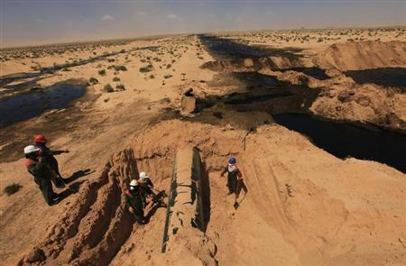 Workers repair a section of an oil pipeline after an explosion, 18 km (11 miles) south of the city of Ajdabiyah April 3, 2013. REUTERS/Esam Al-Fetori