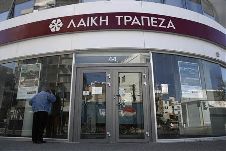 A man tries to look inside a branch of Laiki Bank a few hours before the re-opening of the banks on the island in Nicosia in this March 28, 2013 file photo. REUTERS/Yorgos Karahalis/Files