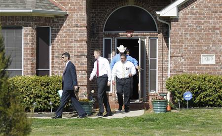 Investigators exit the home of Kaufman County District Attorney Mike McLelland near Forney, Texas April 1, 2013. REUTERS/Tim Sharp