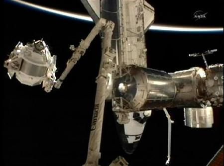 The Alpha Magnetic Spectrometer 02 is moved to the International Space Station aboard the station's robot arm for installation on the orbiting laboratory with the shuttle Endeavour and the Earth's horizon as a backdrop is this still image from NASA TV May 19, 2011. REUTERS/NASA TV/Handout