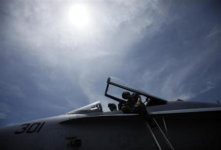 Crew members work on the cockpit of a F/A-18C fighter jet on the deck of the USS Ronald Reagan (CVN76) in Hong Kong August 12, 2011. REUTERS/Tyrone Siu