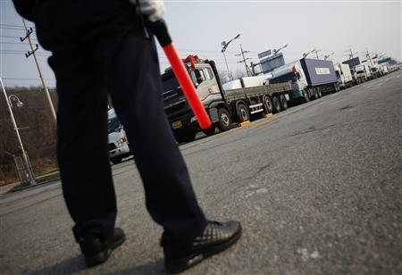 A South Korean security guard keeps watch as South Korean trucks wait to enter the Kaesong industrial complex in North Korea, at the South's Customs, Immigration and Quarantine (CIQ) area, just south of the demilitarised zone separating the two Koreas, in Paju, north of Seoul, April 4, 2013. REUTERS/Kim Hong-Ji