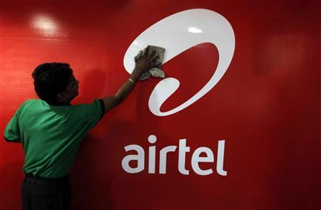 A worker cleans a Bharti Airtel logo inside its shop in Kolkata February 2, 2011. REUTERS/Rupak De Chowdhuri/Files
