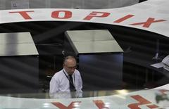 Трейдер работает в торговом зале Токийской фондовой биржи, 30 декабря 2010 года. Японский фондовый рынок вырос в четверг благодаря решениям Банка Японии, а южнокорейские акции снизились из-за угроз с Севера. REUTERS/Kim Kyung-Hoon