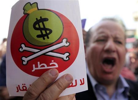Egyptian protesters hold placards with the Arabic inscription reading 'danger' and shout slogans as they demonstrate against the International Monetary Fund (IMF) delegation visit, in front of the General-Prosecutor's office in Cairo April 3, 2013. REUTERS/Mohamed Abd El Ghany