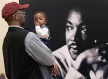 Brendon Barclay holds son Bryce as he visits the Morehouse College Martin Luther King, Jr. collection at the Atlanta History Center which opened on the King Holiday in Atlanta, Georgia, January 15, 2007. REUTERS/Tami Chappell