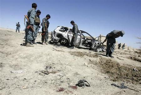 Afghan police stand near destroyed vehicles as they investigate at the site of an air strike in the southeastern town of Ghazni March 30, 2013. REUTERS/Mustafa Andaleb/Files