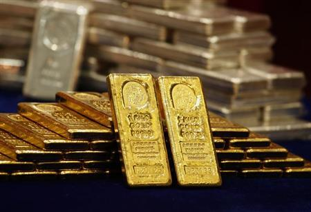 One-kg 24K gold and silver bars are displayed at the Chinese Gold and Silver Exchange Society, Hong Kong's major gold and silver exchange, during the first trading day after the Chinese New Year holidays, in Hong Kong February 14, 2013. REUTERS/Bobby Yip