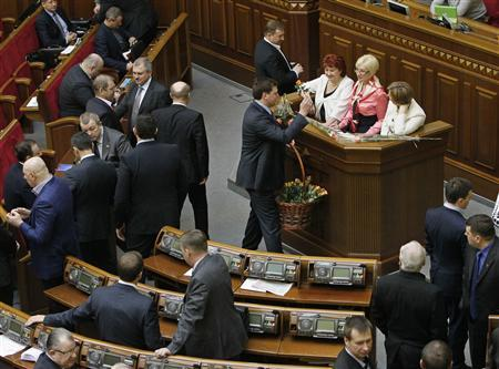 A deputy of Ukrainian President Viktor Yanukovich's Party of the Regions congratulates female opposition deputies as they block the speaker's rostrum to protest against a court ruling to strip Serhiy Vlasenko, their colleague and the lawyer of jailed former Prime Minister Yulia Tymoshenko, of his parliament deputy mandate during a session of the Ukrainian parliament in Kiev March 7, 2013. REUTERS/Gleb Garanich (UKRAINE - Tags: POLITICS ANNIVERSARY) - RTR3EOGJ