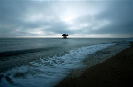 The tide rises near a rig on the beach next to Sizewell Nuclear Plant in Suffolk, eastern England November 29, 2005. REUTERS/Dylan Martinez