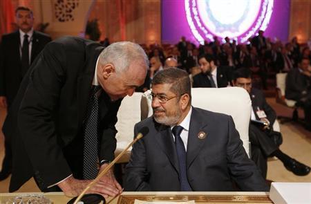 Egypt's President Mohamed Mursi (R) speaks to Egypt's Foreign Minister Mohamed Kamel Amr during the opening of the Arab League summit in Doha March 26, 2013. REUTERS/Ahmed Jadallah