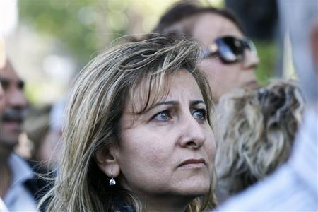 A woman looks on as she joins other Cypriot bank workers during a protest against the possibility of their pensions being affected should the government decide to restructure Cyprus' two largest banks, outside parliament in Nicosia April 4, 2013. REUTERS/Andreas Manolis