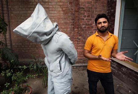 Saud Baloach, 28, a fine art artist, stands near his sculpture called ''No Fear'' during an interview with Reuters at Government College University in Lahore March 22, 2013. REUTERS/Mohsin Raza
