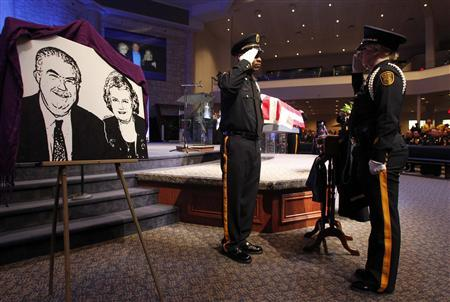 Two police officers salute each other next to a lithograph of Kaufman County district attorney Mike McLelland and his wife Cynthia, during a change of guard at a memorial service in Sunnyvale, Texas April 4, 2013. REUTERS/Mike Stone