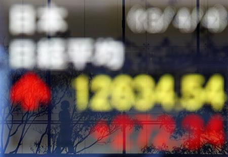 A passerby is reflected in an electronic board showing Japan's Nikkei average outside a brokerage in Tokyo April 4, 2013. REUTERS/Yuya Shino